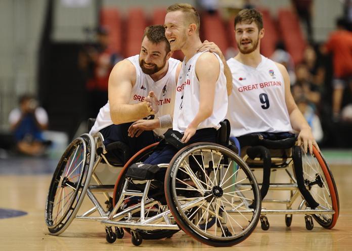 Male wheelchair basketball player Gregg Warburton hugged by teammate
