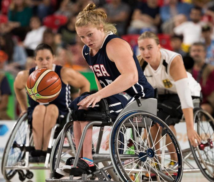 Wheelchair basketball player Rose Hollermann rolls with the ball