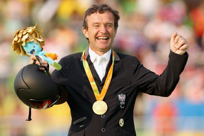 Male Para equestrian rider Pepo Puch raises his arms to celebrate with a gold medal around his neck