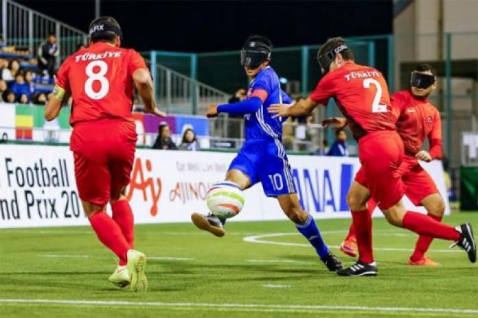 um jogador de futebol japonês cego dribla a bola em dois oponentes