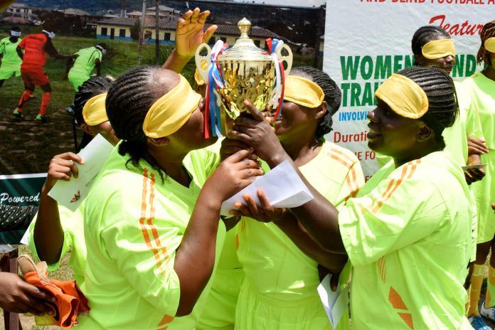 Quatro jogadores de futebol cegos beijando um troféu
