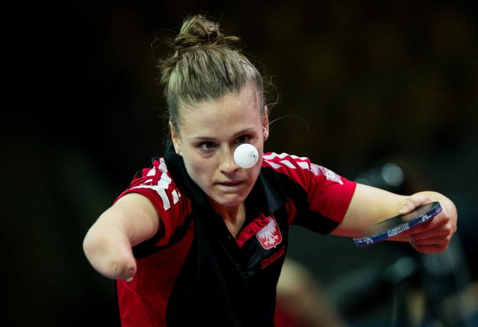 Natalia Partyka competing at the World Para Table Tennis Championships, holding the bat and looking closely at the ball