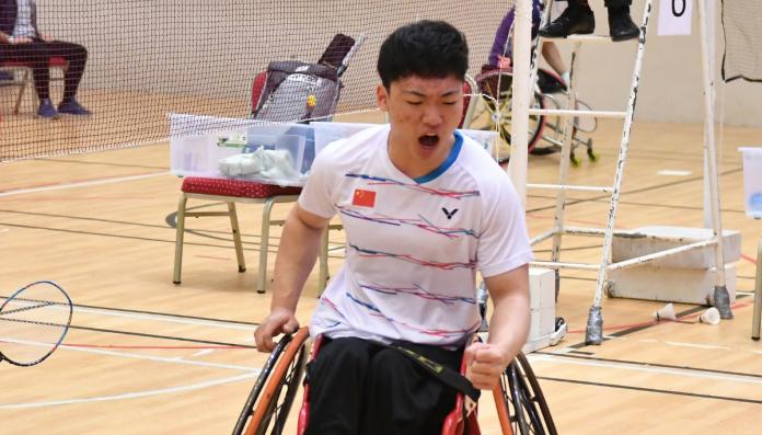 wheelchair para-badminton player pumps his fist after winning a point