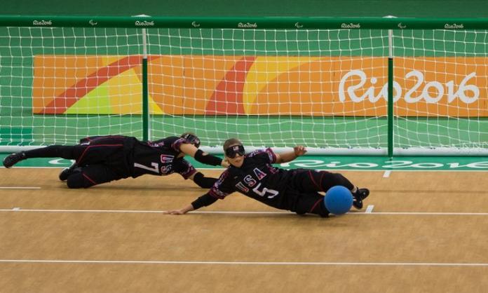 Goalball players Eliana Mason and Amanda Dennis dive to stop the ball