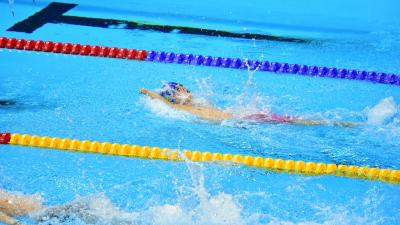 a male Para swimmer competing in a backstroke race