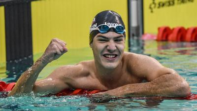 a male swimmer in the water giving a victory fist pump