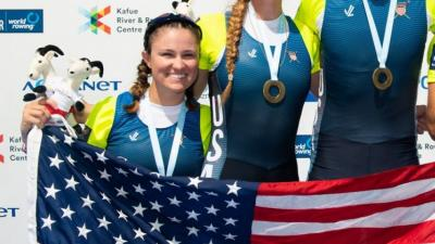 Female rower smiles on podium holding USA flag
