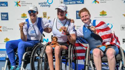 Three female rowers in wheelchairs pose with their medals