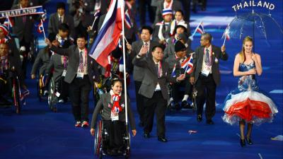 Thai woman in wheelchair leading her delegation as the flag bearer