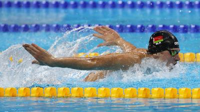 Male swimmer in water competing in butterfly stroke