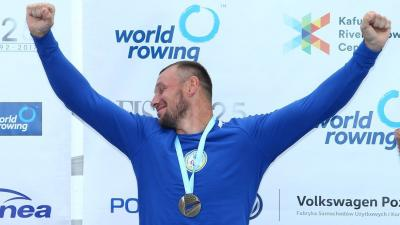 rower raises arms to celebrate gold medal on podium