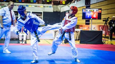 Two male taekwondo athletes fight