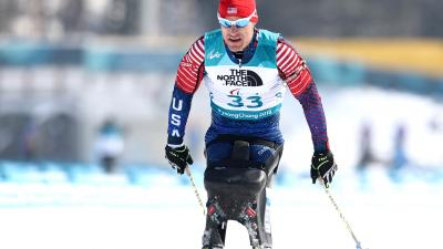 a male Para sit skier crosses the finish line