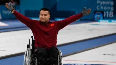 a male wheelchair curler raises his arms in celebration