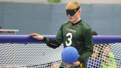 a male goalball player stands at the net