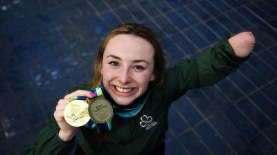 female Para swimmer Ellen Keane smiles and holds up her gold medal