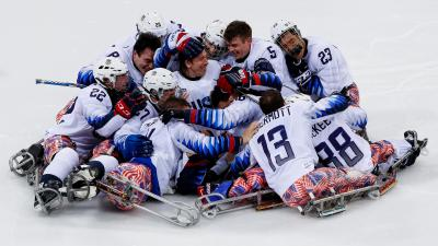 male USA ice hockey players celebrate hugigng in a big group on the ice