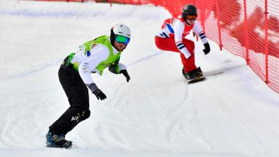 two male Para snowboarders racing down the slope head to head