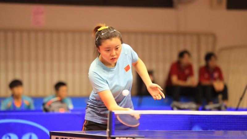 Chinese female table tennis player hits a return ball