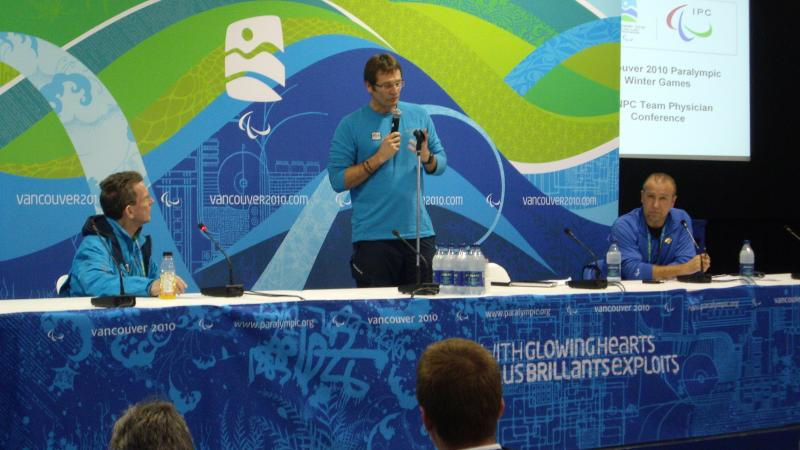 A man standing up and speaking in front of a Vancouver 2010 backdrop