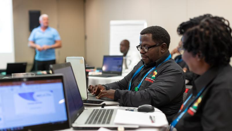 Delegates from NPC Guyana work with their laptops during OCP workshop