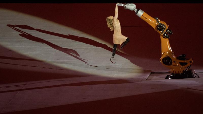 a female with prosthetic legs being raised into the air holding onto a robot arm