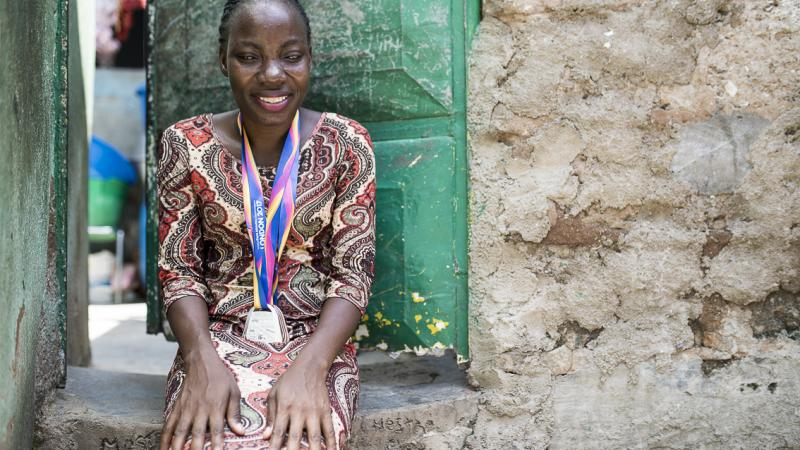 Angolan sprinter Esperanca Gicasso poses for a picture in front of her house with the two medals she won at the London 2017 World Para Athletics Championships