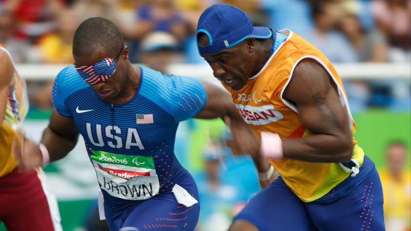 A male blind runner with a USA flag blindfold on sprints alongside his guide