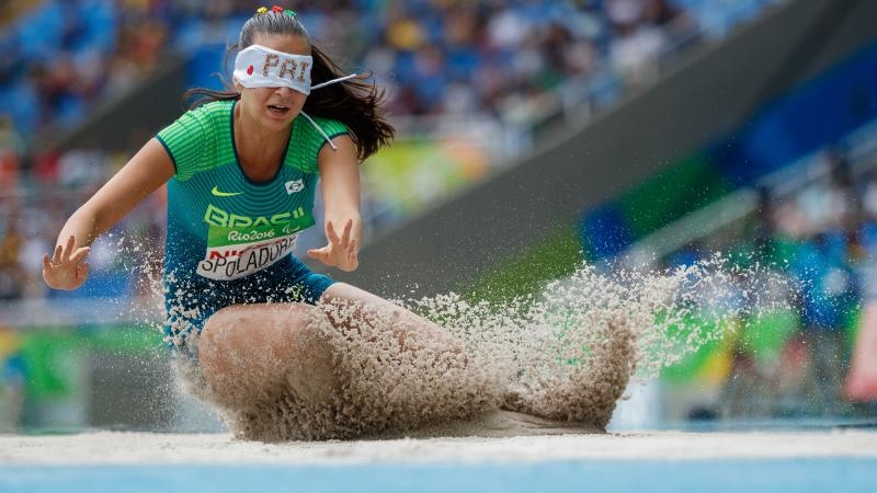 a female long jumper wearing a blindfold jumps into sand