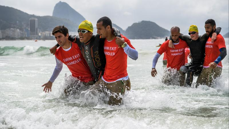 two male triathletes without legs being carried out of the sea in Rio