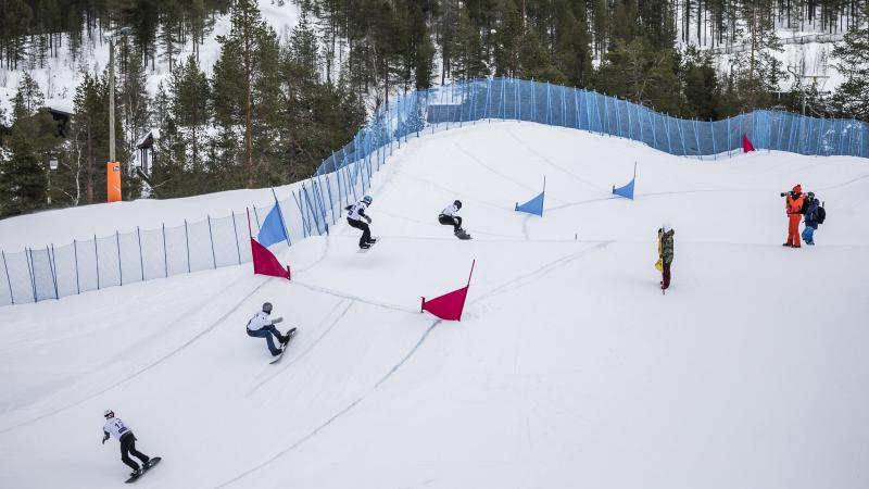 Four male snowboarders competing