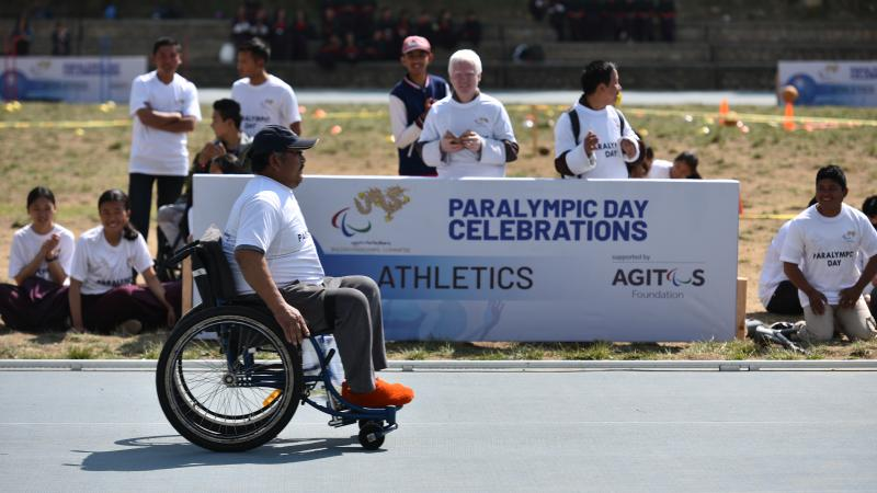 Wheelchair user in front of Bhutan's Paralympic Day Celebrations signage in Thimpu