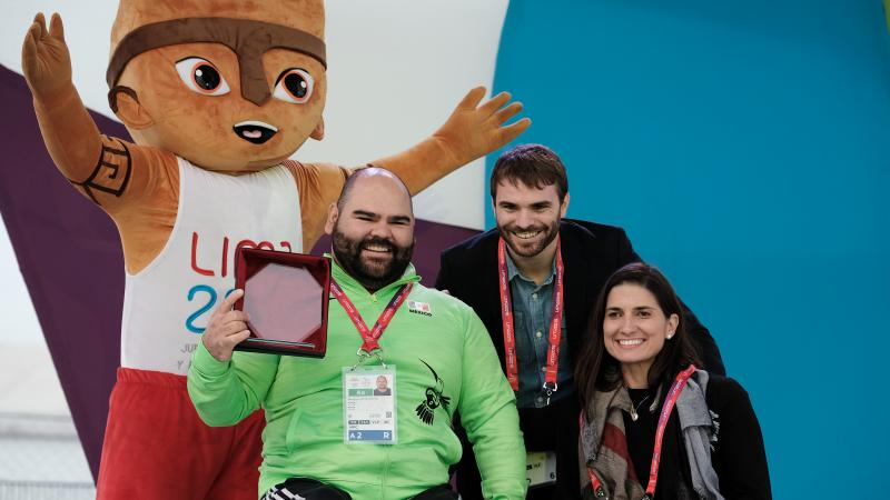 A male powerlifter holds up an award smiling with two other people and a furry mascot standing behind