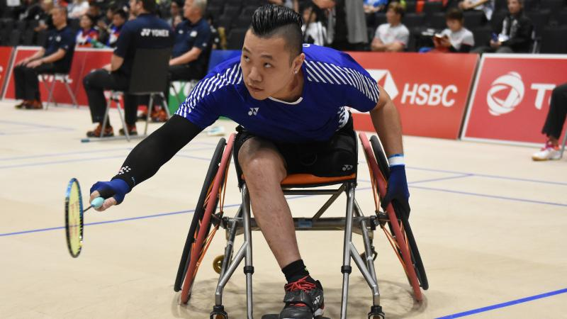 Hong Kong badminton player in wheelchair leans over to return a shot