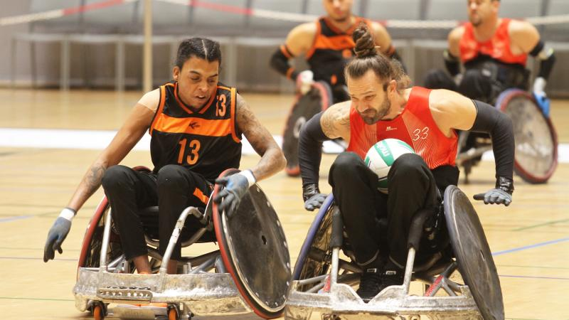 Two male wheelchair rugby players clash chairs
