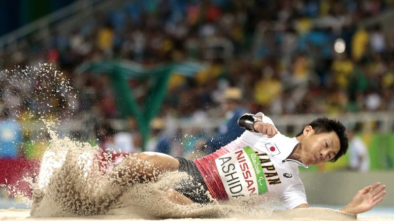 Japanese man completes long jump in sand