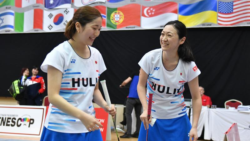 two female standing Para badminton players laughing together on court