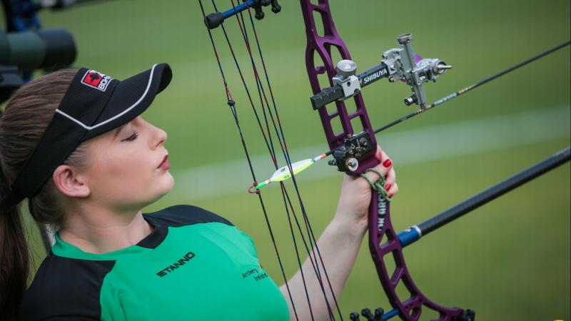 Female Irish archery looks her her bow and arrow