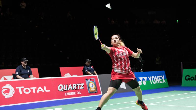 Indonesia female badminton player lunges for the shuttle