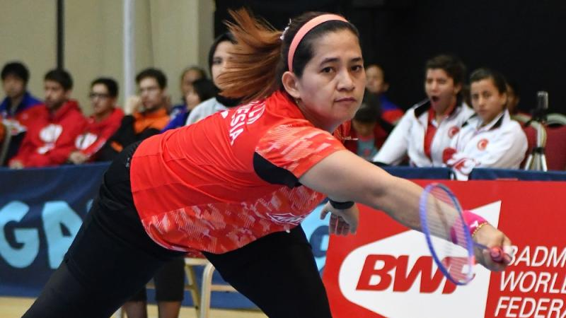 A female Para badminton player leans down to hit a forehand