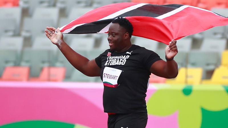 a male Para athlete holding up the Trinidad and Tobago flag