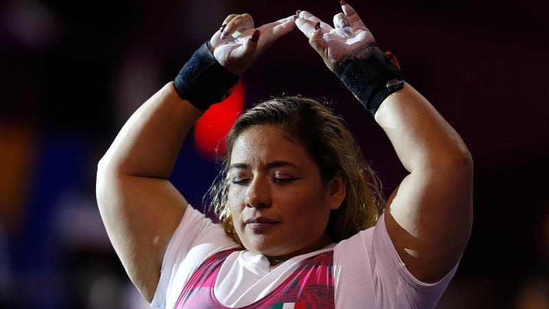 a female powerlifter raises her arms above her head in preparation for her lift
