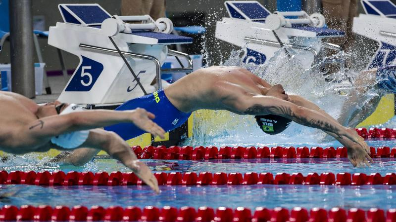 a male Para swimmer jumps backwards into the water
