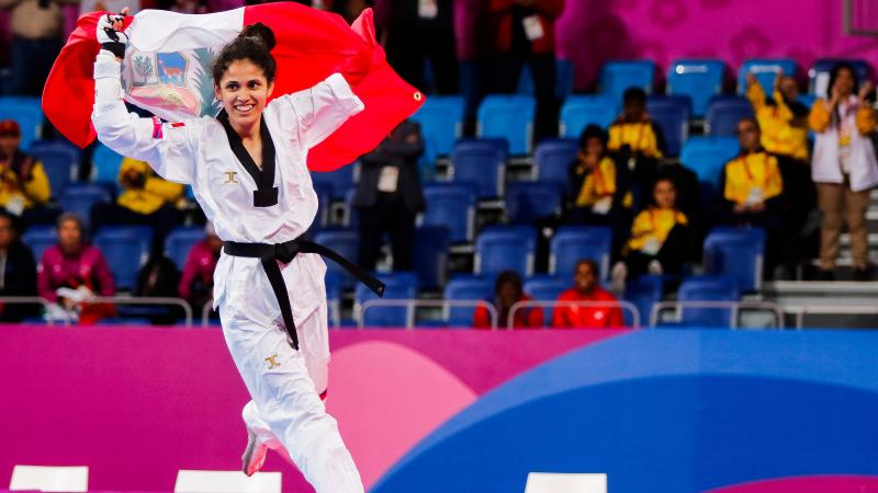 a female Para taekwondo athlete carrying the Peru flag