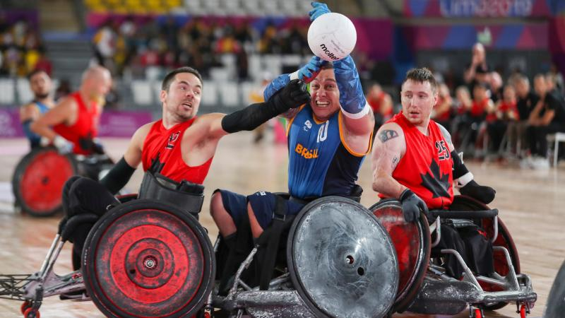 male wheelchair rugby players fight for the ball