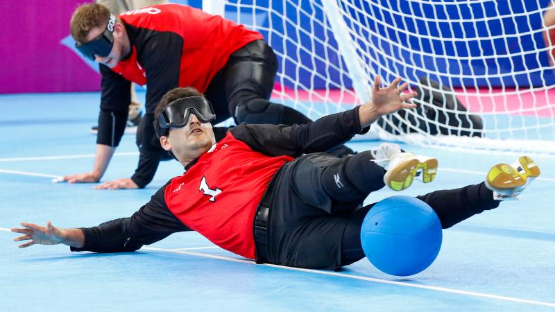 a male goalball player saves a shot with his legs
