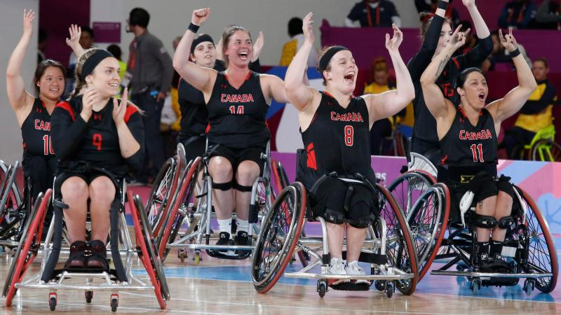a group of female wheelchair basketball players cheering