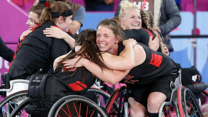a group of female wheelchair basketball players hugging