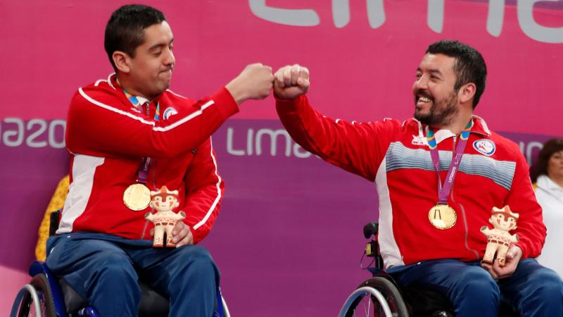 two male wheelchair table tennis players bump fists