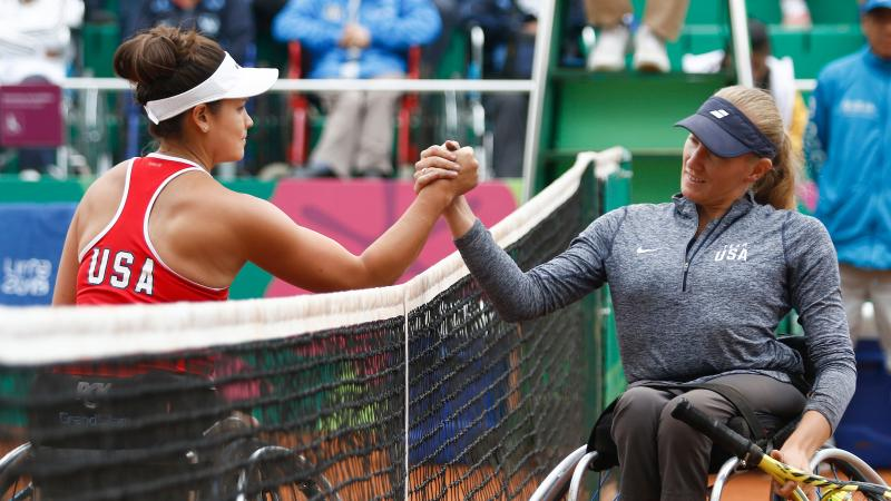 two female wheelchair tennis players high five over the net